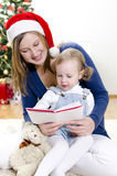 Girl and her mom reading book Stock Photos