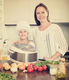 Girl and her mom with rice cooker Stock Images
