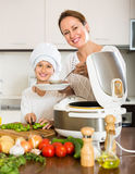 Girl and her mom with rice cooker Royalty Free Stock Photo