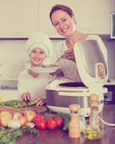 Girl and her mom with rice cooker Stock Image