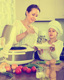 Girl and her mom with rice cooker Royalty Free Stock Photography