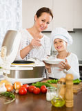 Girl and her mom with rice cooker Royalty Free Stock Image