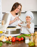 Girl and her mom with rice cooker Stock Photography