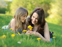 Girl with her mommy. Girl and mother on the green grass Stock Photos