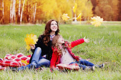 Girl and her mother in the autumn park Stock Photos