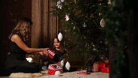 A girl and her mother are collecting New Year`s gifts under a Christmas tree.  stock video footage