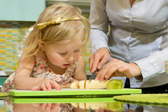 Girl and her mother cutting fruits Royalty Free Stock Images