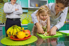 Girl and her mother cutting fruits Royalty Free Stock Photography
