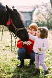 Girl and her mother feeding horse Stock Photos