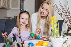 Girl with her mother learning to paint Easter eggs Royalty Free Stock Images