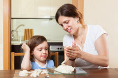 A girl with her mother learns to mold dough figurines in home Stock Image