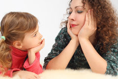Girl and her mother lies on fell, hands on chin Stock Photography