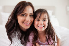 Girl and her mother lying on a bed. While looking at the camera Stock Photography