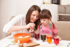 The girl and her mother paint eggs at home Stock Photos