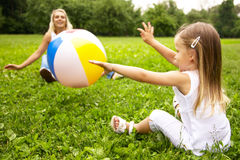 Girl and her mother are playing with ball. Little girl and her mother are playing with ball; shallow DOF, foces on girl Royalty Free Stock Image
