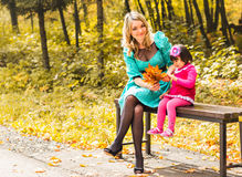 Girl and her mother playing outdoors with autumnal maple leaves. Baby girl picking golden leaves. Mother and daughter play in autumn park. Parent and child walk Stock Photos