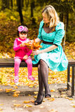 Girl and her mother playing outdoors with autumnal maple leaves. Baby girl picking golden leaves. Mother and daughter play in autumn park. Parent and child walk Royalty Free Stock Image