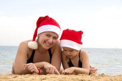 Girl with her mother in a santa hat on the beach Stock Photo