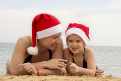 Girl with her mother in a santa hat on the beach Stock Photography