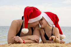 Girl with her mother in a santa hat on the beach Stock Photos
