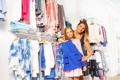 Girl with her mother shopping and hold chosen item Stock Photography