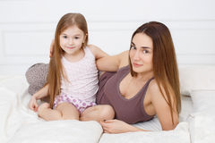 The girl and her mother sitting on white bed Stock Image
