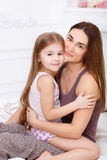 The girl and her mother sitting on white bed Stock Photos