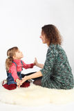 Girl and her mother sitting on white fell Stock Photo