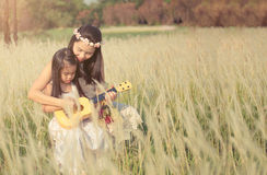 Girl is with her mother to meadow outdoor in nature on sunny day Royalty Free Stock Photo