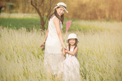 Girl is with her mother to meadow outdoor in nature on sunny day Royalty Free Stock Images