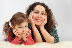 Girl and her mother with toothy smile lies on fell stock photo