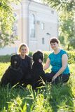 The girl and her mother and two black Russian Terrier sitting on the grass in the Park. Telephoto shot stock image