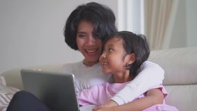 Girl and her mother use laptop on sofa stock video footage