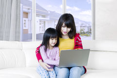Girl and her mother using laptop at home Stock Images