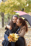 Girl with her mother and yellow leaves Stock Photo