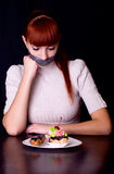 Girl with her mouth sealed with adhesive tape and cakes Royalty Free Stock Photos