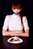 Girl with her mouth sealed with adhesive tape and cakes Stock Photos