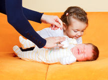 Girl with her newborn brother. Young sister kissing her newborn adorable brother Stock Photos