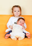 Girl with her newborn brother. Young sister playingwith  her newborn adorable brother Royalty Free Stock Photos