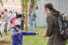 Girl with her old relative play `blind`s man buff` in the park. Opening the art park `New Holland` in the Saint-Petersburg, Russia, 28 August 2016. Girl with her stock photos