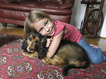 Girl with her pet dog. Cute young girl cuddling her pet dog at home Stock Image