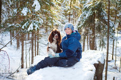 Girl with her pet dog outdoors. Pretty young girl with her pet springer spaniel outdoors in a winter forest back-lit by the sun Stock Image