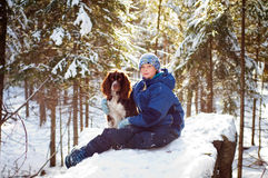 Girl with her pet dog outdoors. Pretty young girl with her pet springer spaniel outdoors in a winter forest back-lit by the sun Stock Photo