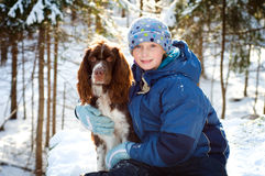 Girl with her pet dog outdoors. Pretty young girl with her pet springer spaniel outdoors in a winter forest back-lit by the sun Stock Photography