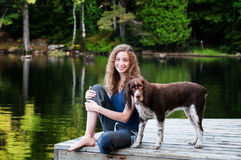 Girl and her pet dog. Teen girl sitting on a dock by a lake in Haliburton Ontario with her dog royalty free stock photography