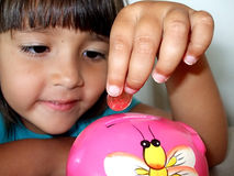 Girl and her piggy bank Royalty Free Stock Photos