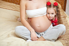 A girl and her pregnant mother Royalty Free Stock Image