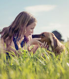 Girl with her puppy in the grass Stock Image