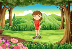 A girl in her red uniform standing at the forest Royalty Free Stock Photography