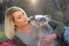 Girl and her schnauzer dog. Outdoor portrait. Blonde 23 year old, dog, sunset,  in the field Royalty Free Stock Photography